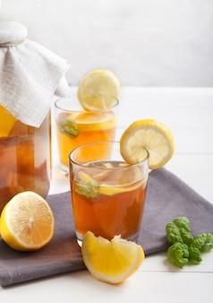 Dois copos e um banco com kombuchá e rodelas de limão em uma mesa branca