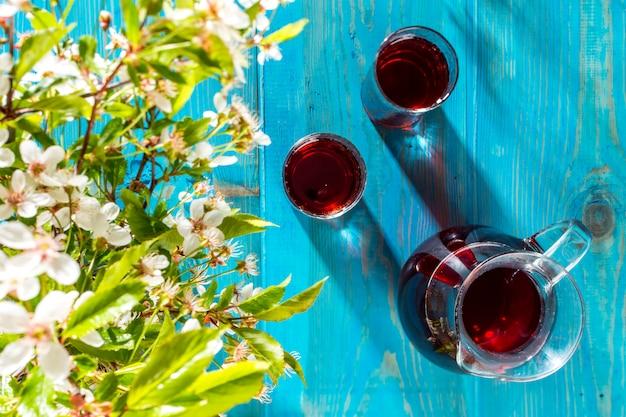 Dois copos e uma jarra de suco de cereja em cima da mesa