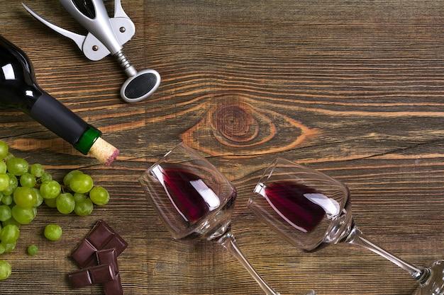 Dois copos, garrafa de vinho tinto e uva em uma mesa de madeira. vista do topo. copie o espaço. postura plana. natureza morta