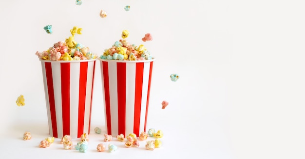 Dois copos grandes cheios com pipoca doce colorida para se divertir assistindo filmes no cinema