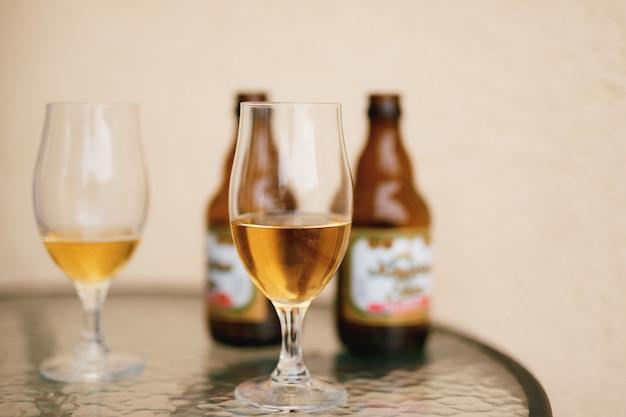 Dois copos meio cheios de cerveja em um fundo desfocado com garrafas de cerveja na mesa