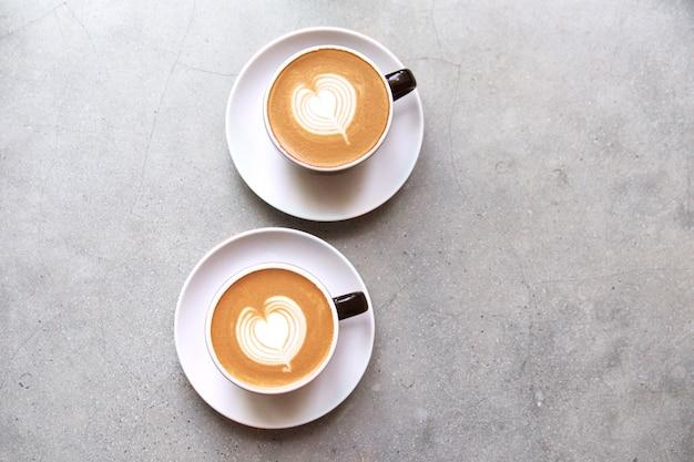 Dois copos pretos do cappucino saboroso com latte da arte do amor.