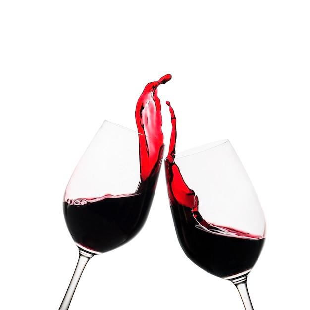 Dois copos tinindo de vinho tinto em um brinde