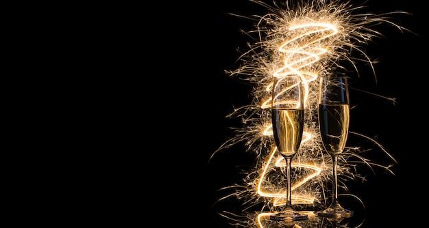Dois copos transparentes de champanhe nas luzes de bengala