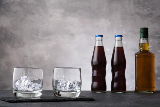Dois copos transparentes vazios e garrafas cheias de cola e uísque