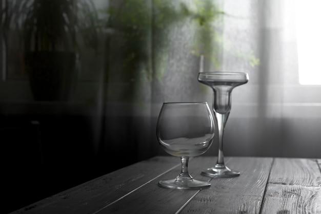 Dois copos vazios colocados em uma mesa de madeira no fundo de uma janela