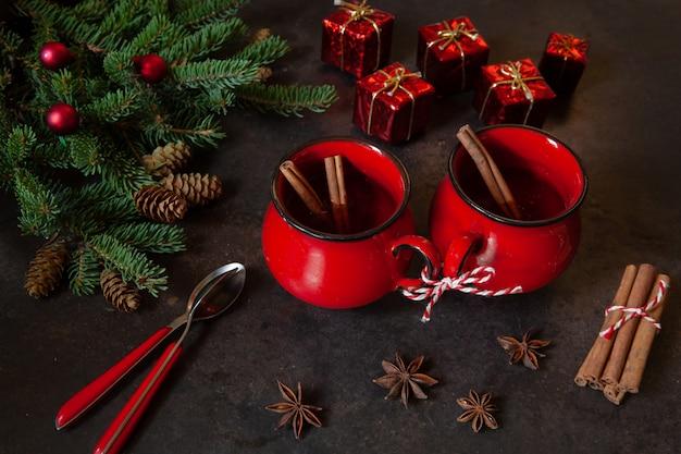 Dois copos vermelhos com bebida picante de natal quente com bolos.