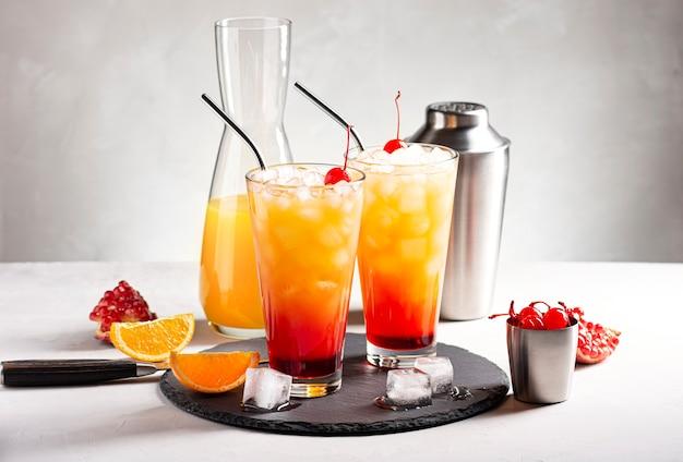 Dois coquetéis alcoólicos sunrise com tequila ao lado de uma coqueteleira, uma garrafa de suco e fatias de frutas