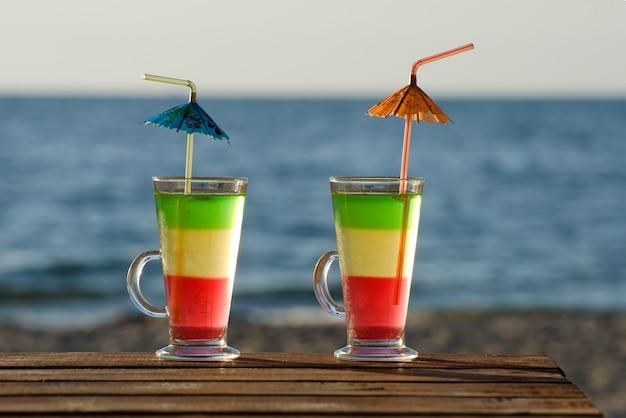 Dois coquetéis coloridos em uma mesa de madeira na praia, o mar na parede