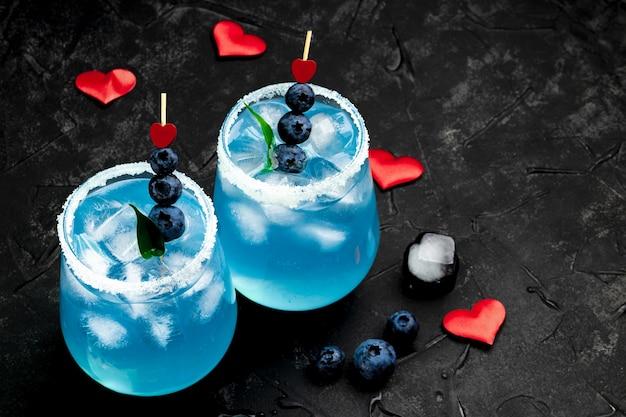Dois coquetéis com gelo, curaçao azul e mirtilos
