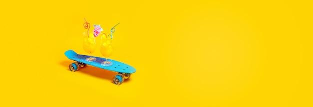 Dois coquetéis com suco de laranja e cubos de gelo em um skate azul