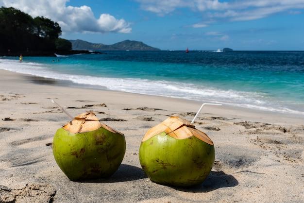 Dois coquetéis de coco fresco na bela praia em dia ensolarado