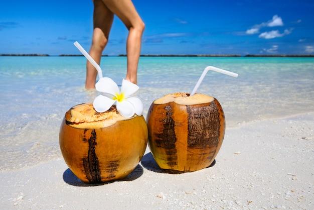 Dois coquetéis de coco na praia de areia branca.