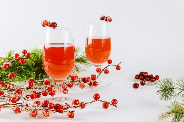 Dois coquetéis de cranberry com cranberry fresco em fundo branco.