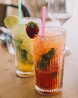 Dois coquetéis de mojito feitos com rum envelhecido de hortelã e frutas diferentes