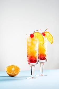 Dois coquetéis festivos de tequila sunrise em um fundo azul e branco ao lado de uma fatia de laranja