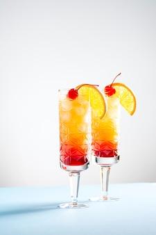 Dois coquetéis festivos de tequila sunrise em um fundo branco e azul