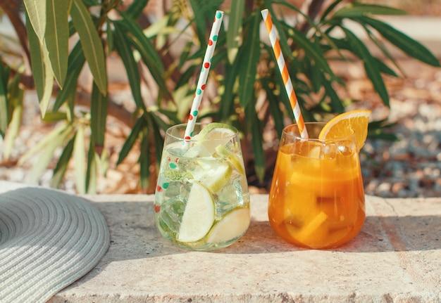 Dois coquetéis refrescantes perto de plantas de jardim e chapéu de palha de perto