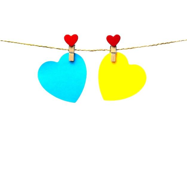 Dois corações azuis e amarelos, pendurado em uma corda anexada com reboques