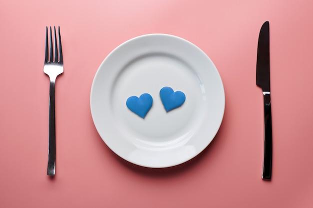 Dois corações azuis no prato. namoro romântico. jantar sem discriminação contra as minorias sexuais. preparação de banquetes de casamento lgbt.