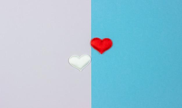 Dois corações brancos e vermelhos em dois lados do fundo.