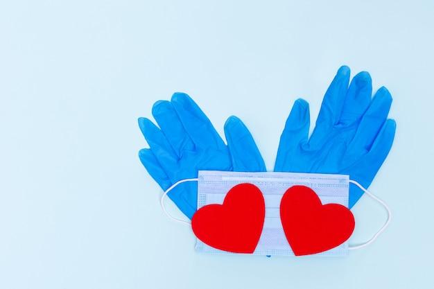 Dois corações de amor de papel vermelho em uma máscara de proteção azul e luvas de proteção azuis