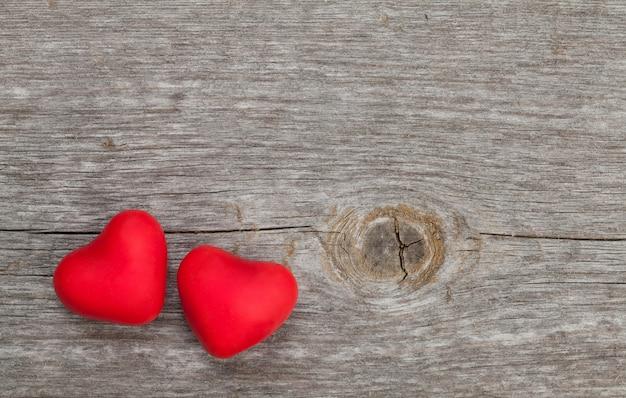 Dois corações de bombom vermelho em fundo de madeira