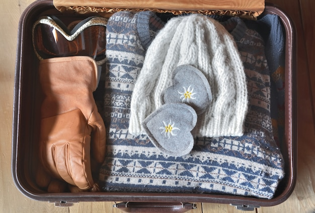 Dois corações de feltro colocados em uma mala com roupas quentes