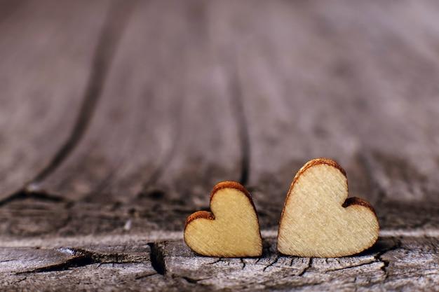 Dois corações de madeira bem colocados em um fundo de madeira vintage