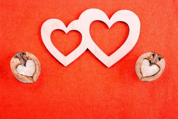 Dois corações de madeira e duas nozes em forma de coração estão no papel vermelho e copiam o espaço abaixo deles.