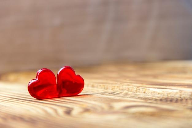 Dois corações de madeira em uma mesa rústica com luz solar