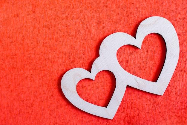 Dois corações de madeira esculpidos estão deitado na diagonal em papel texturizado vermelho