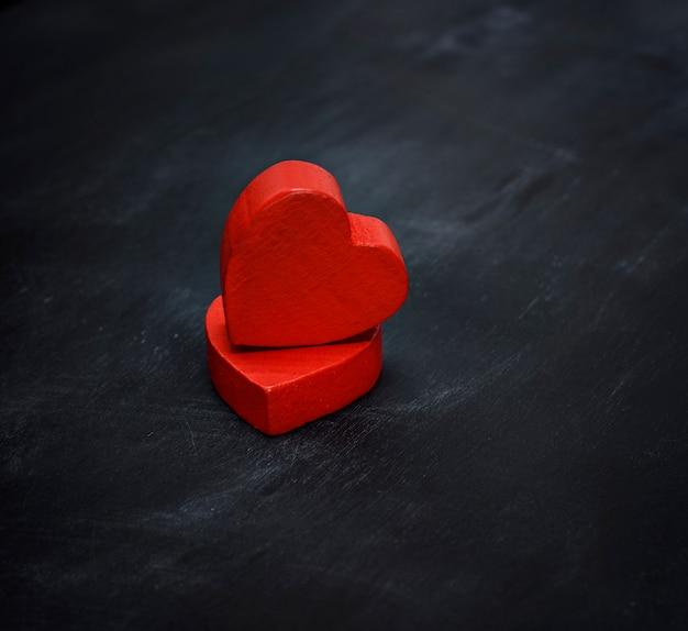 Dois corações de madeira vermelhos sobre um fundo preto