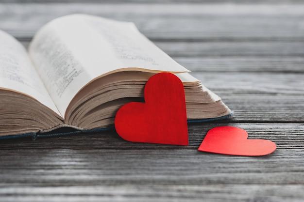 Dois corações de papel vermelho e livro aberto na mesa de madeira