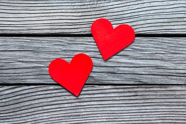 Dois corações de papel vermelho na madeira texturizada cinza