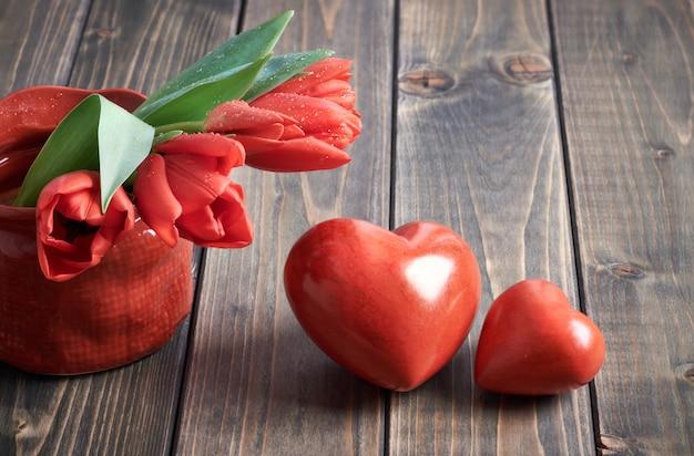 Dois corações de pedra e bando de tulipas vermelhas em fundo de madeira