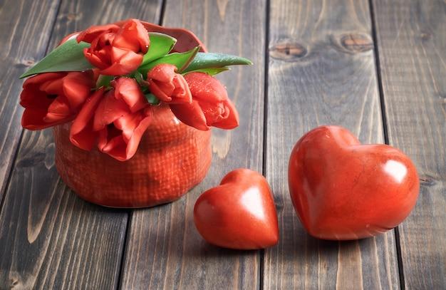 Dois corações de pedra e ramo de tulipas vermelhas