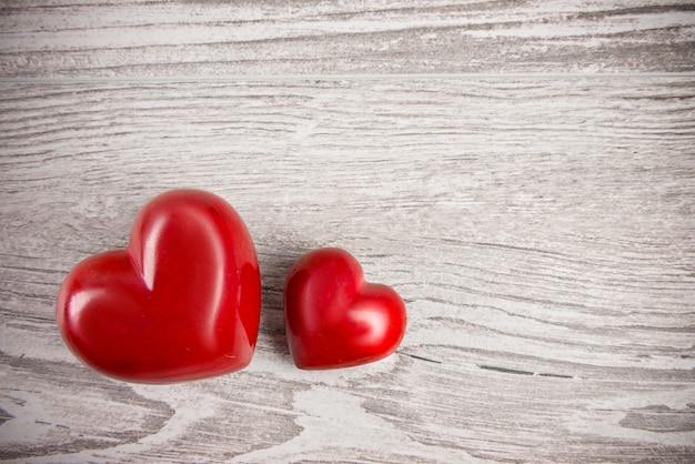 Dois corações de pedra vermelhos em fundo neutro, espaço de texto
