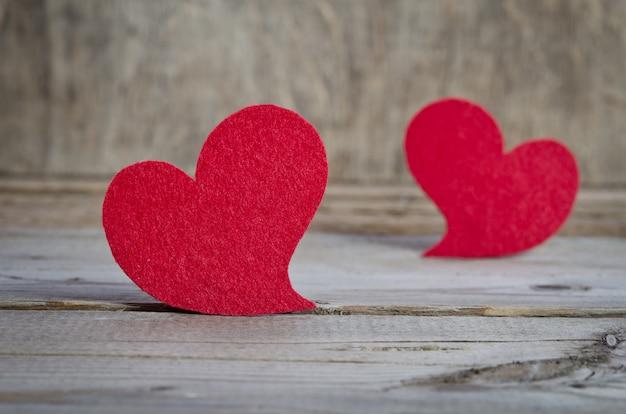 Dois corações de tecido vermelho em pé sobre uma placa de madeira na mesa de madeira