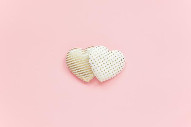 Dois corações de têxteis com padrão de ouro sobre fundo rosa, composição central, estilo minimalista