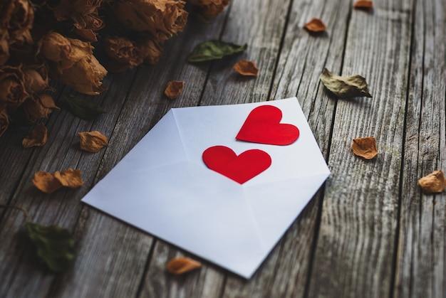 Dois corações em envelope, pétalas de rosas secas na mesa de madeira