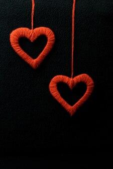 Dois corações em um fundo preto, corações feitos de fios. decoração de dia dos namorados