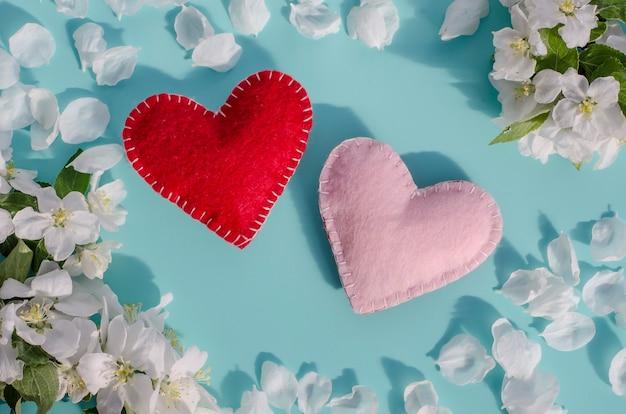 Dois corações feitos à mão em um azul marinho com uma moldura de flores brancas da primavera