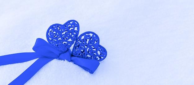 Dois corações na cor azul clássica amarrados com fita azul na neve
