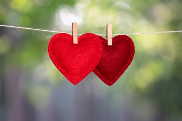 Dois corações pendurados no varal. conceito de amor e dia dos namorados