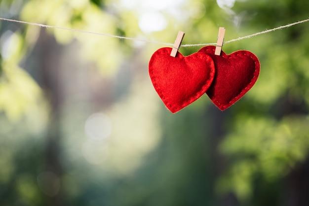 Dois corações pendurados no varal contra um fundo verde. conceito de amor e dia dos namorados