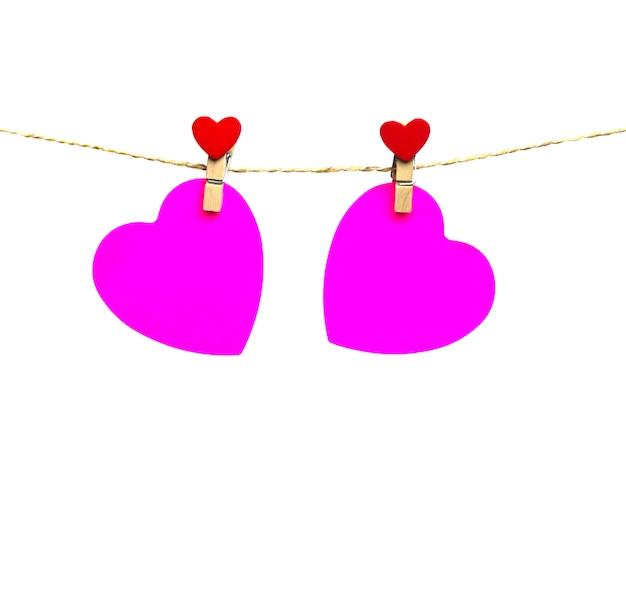 Dois corações rosa pendurado em uma corda anexada com reboques