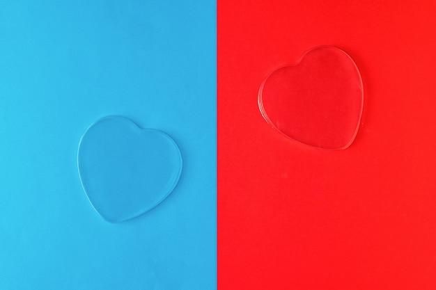 Dois corações transparentes em uma superfície azul e vermelha
