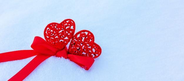 Dois corações vermelhos amarrados com fita vermelha na neve