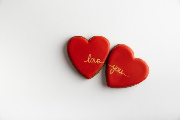 Dois corações vermelhos com as palavras te amo em fundo branco, vista superior. dia dos namorados